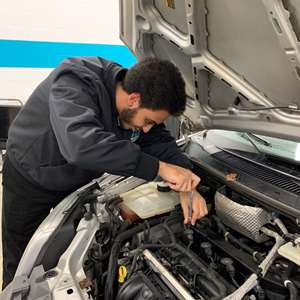 An automotive technician working efficiently on a car to make more money.